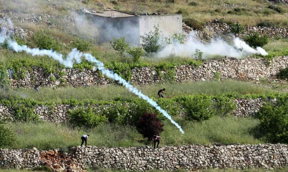 Palestinians run from tear gas fired by Israeli soldiers, during a demonstration against Jewish settlements in the northern West Bank village of Iraq Burin, near Nablus, Saturday, May 21, 2011. (AP Photo/Nasser Ishtayeh) Photo: Nasser Ishtayeh / AP