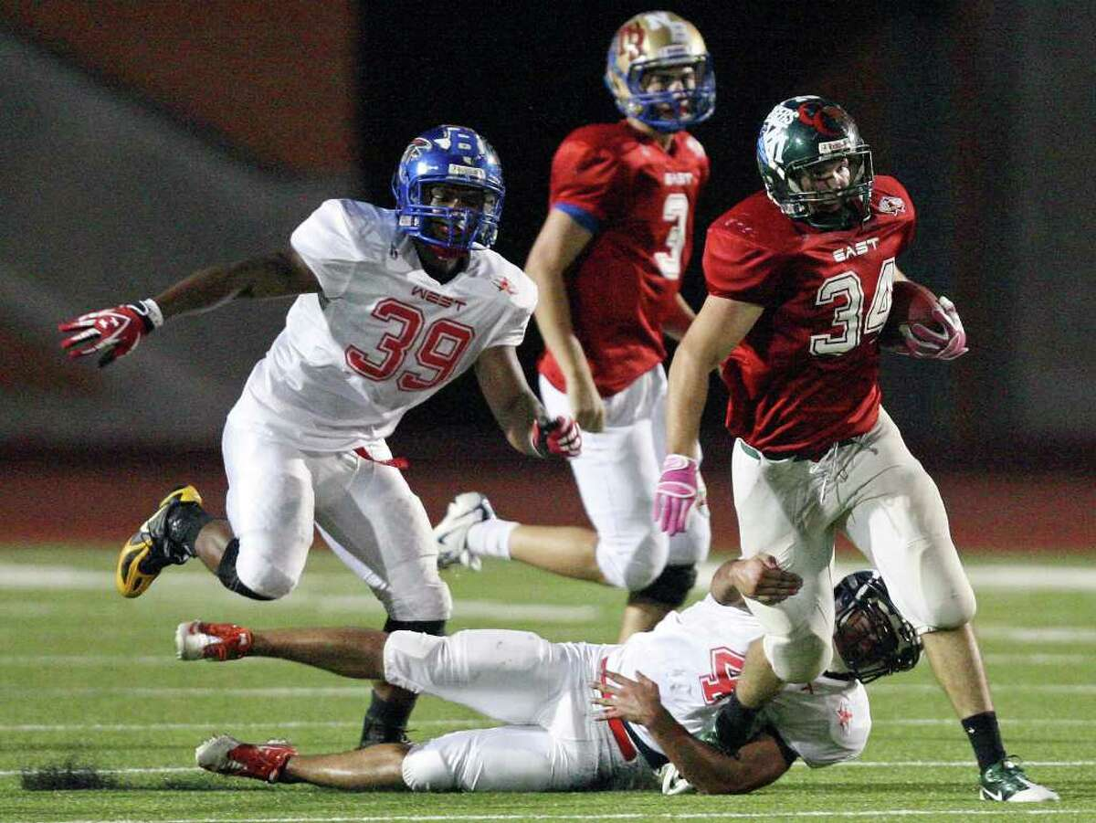 East team's Sean Wolff tries to shake the tackle of West team's Roddy Reyna as West team's Artmanthesis Penilton moves in on the play during first half action of the 33rd annual Pizza Hut High School All-Star Football Game held Saturday May 21, 2011 at Heroes Stadium.