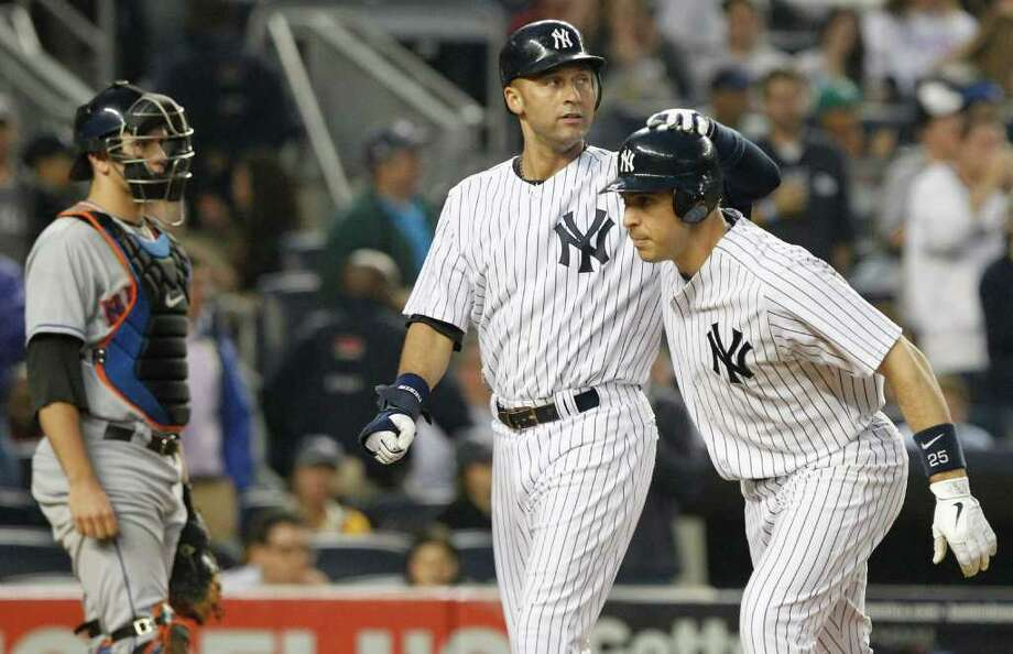 New York Yankees' Derek Jeter, center, celebrates with teammate Mark Teixeira, right, as they pass New York Mets catcher Josh Thole after Teixeira hit a two-run home run during the third inning of an interleague baseball game on Saturday, May 21, 2011, at Yankee Stadium in New York. (AP Photo/Frank Franklin II) Photo: Frank Franklin II