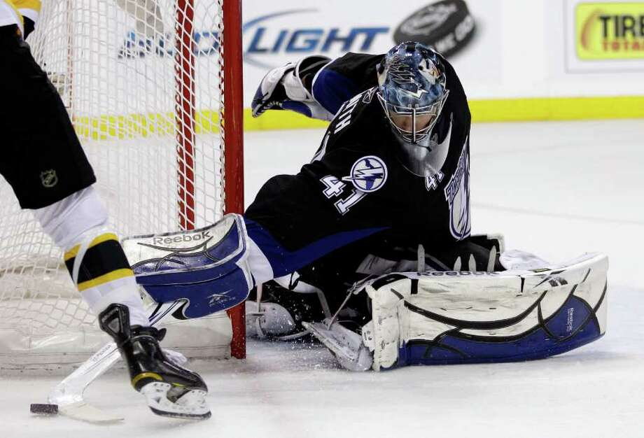 Tampa Bay Lightning goalie Mike Smith reaches for the puck against the Boston Bruins in the third period of Game 4 of the NHL hockey Stanley Cup playoffs Eastern Conference finals, Saturday, May 21, 2011, in Tampa, Fla. The Lightning won 5-3. (AP Photo/Chris O'Meara) Photo: Chris O'Meara