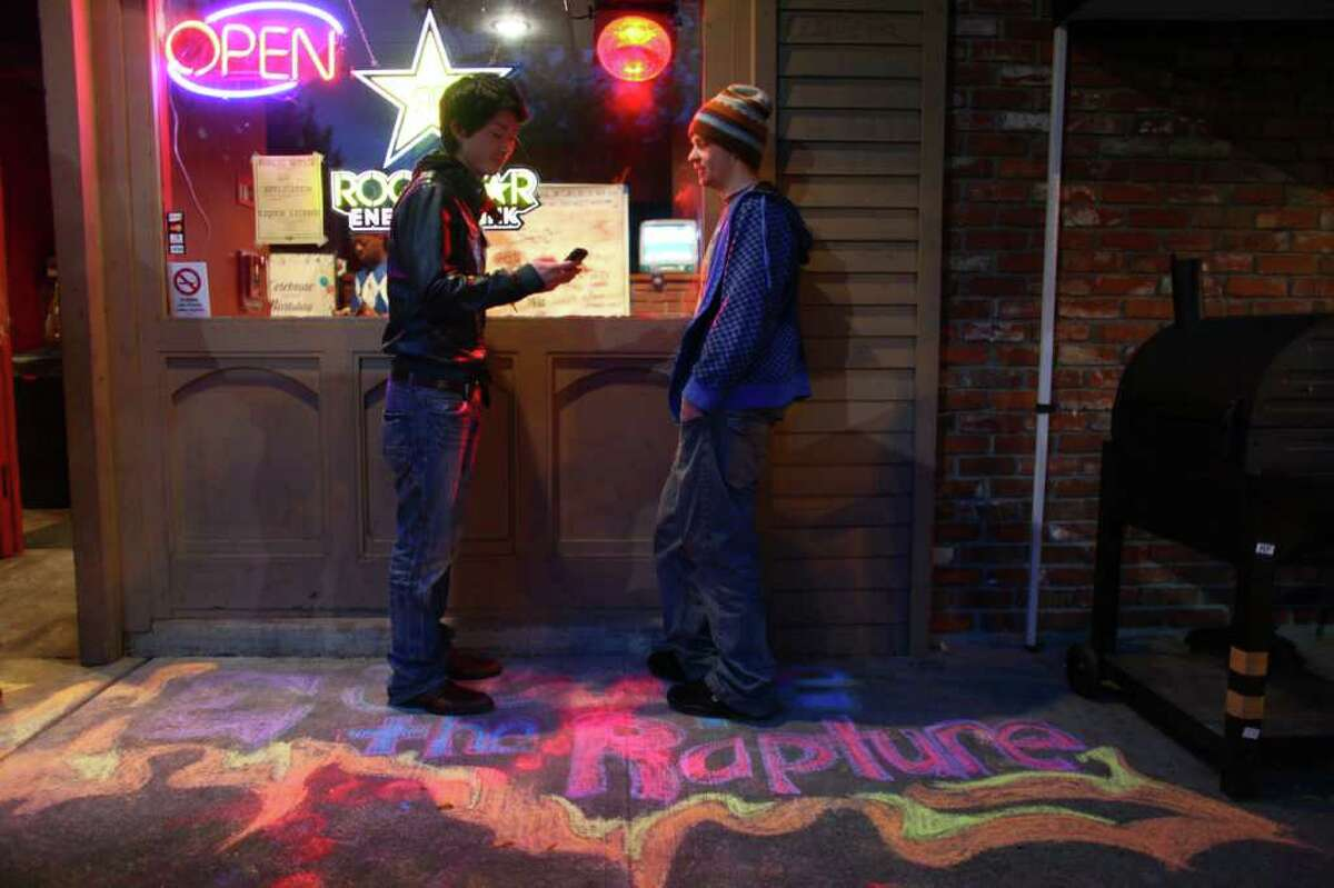 Yuhei Yamamotot, left, and Matthew Duncan of Seattle debate if they will enter a rapture party at Dorky's Arcade in Tacoma.