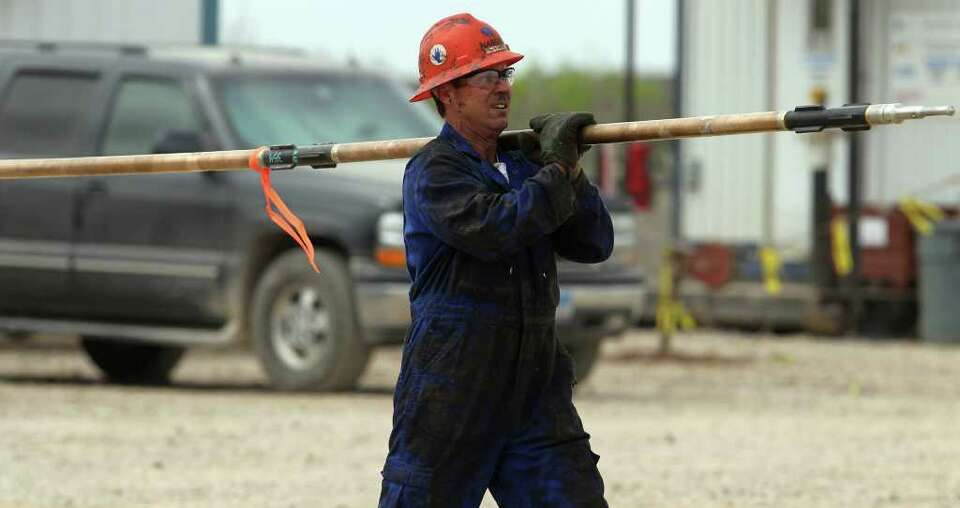 A worker carries a piece of equipment to a rig in McMullen County. Some are predicting developmen