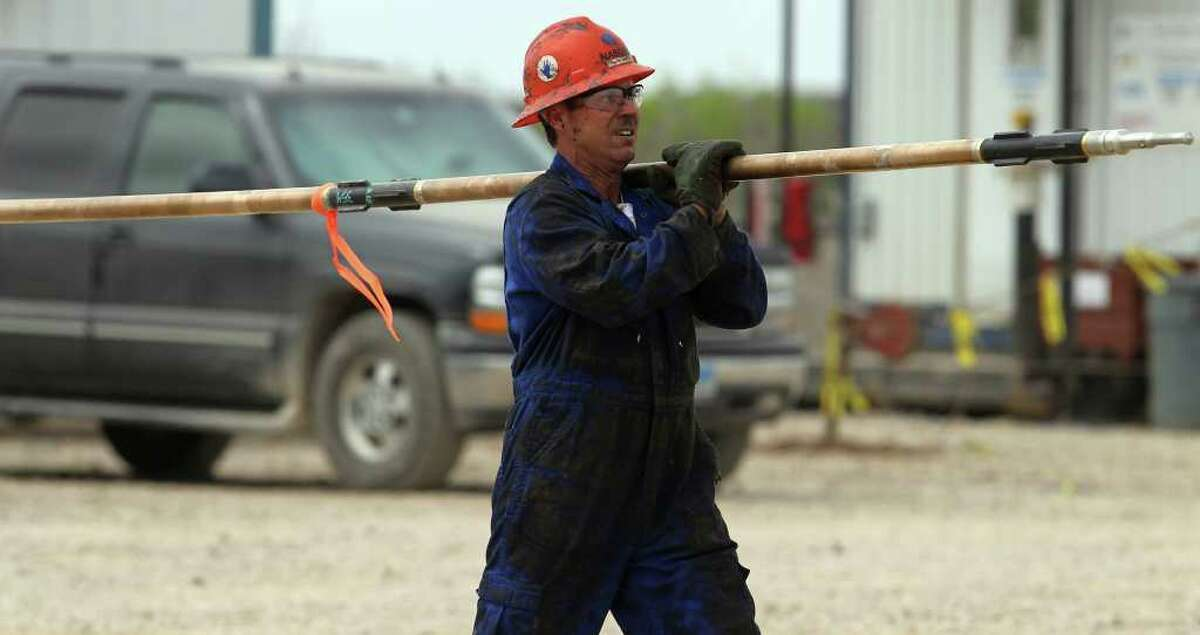 A worker carries a piece of equipment to a rig in McMullen County. Some are predicting development of the Eagle Ford shale will be another Spindletop for Texas.