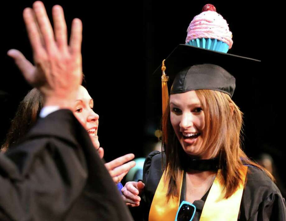 Graduate Margaret Hillery wears a cupcake on her mortar board as she receives her diploma for the Culinary Arts program during the Schenectady County Community College commencement ceremony on Saturday, May 21, 2011, at Proctors in Schenectady, N.Y. (Cindy Schultz / Times Union) Photo: Cindy Schultz