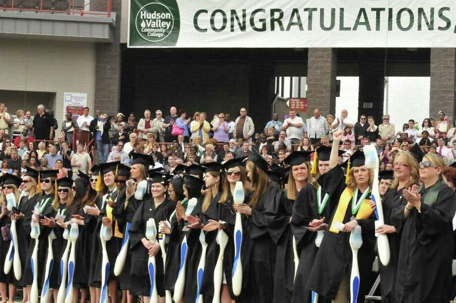 School of Health Science graduates hold giant tooth brushes during the Hudson Valley Community College Commencement Ceremony at the Joseph L. Bruno stadium in Troy, NY Saturday May 21, 2011.( Michael P. Farrell/Times Union ) Photo: Michael P. Farrell