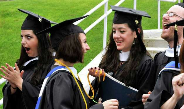 Graduates including Chelsea Pinero, of Southbury, left center, and Samantha Tuozzolo, of Newtown, right center, share a moment before commencement ceremonies at Western Connecticut State University, in Danbury, Sunday, May 22, 2011, Photo: Michael Duffy / The News-Times