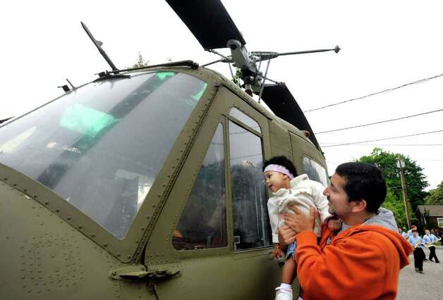 Paulakamilia Navarro, 2, looks at a helicopter from her dad, Mauncio's arms in Bethel's Memorial Day parade, Sunday, May 22, 2011. Photo: Michael Duffy / The News-Times