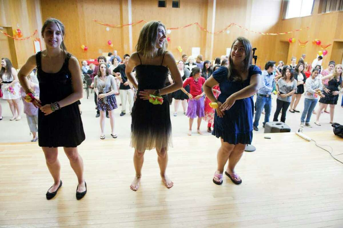 """Rachel Berkrot, left, Brittany Duffin, center, and Alex Salvatore show off their moves as the Stamford High School Student group """"Build On"""" hosts a prom for seniors at the Jewish Community Center in Stamford, Conn., May 22, 2011."""