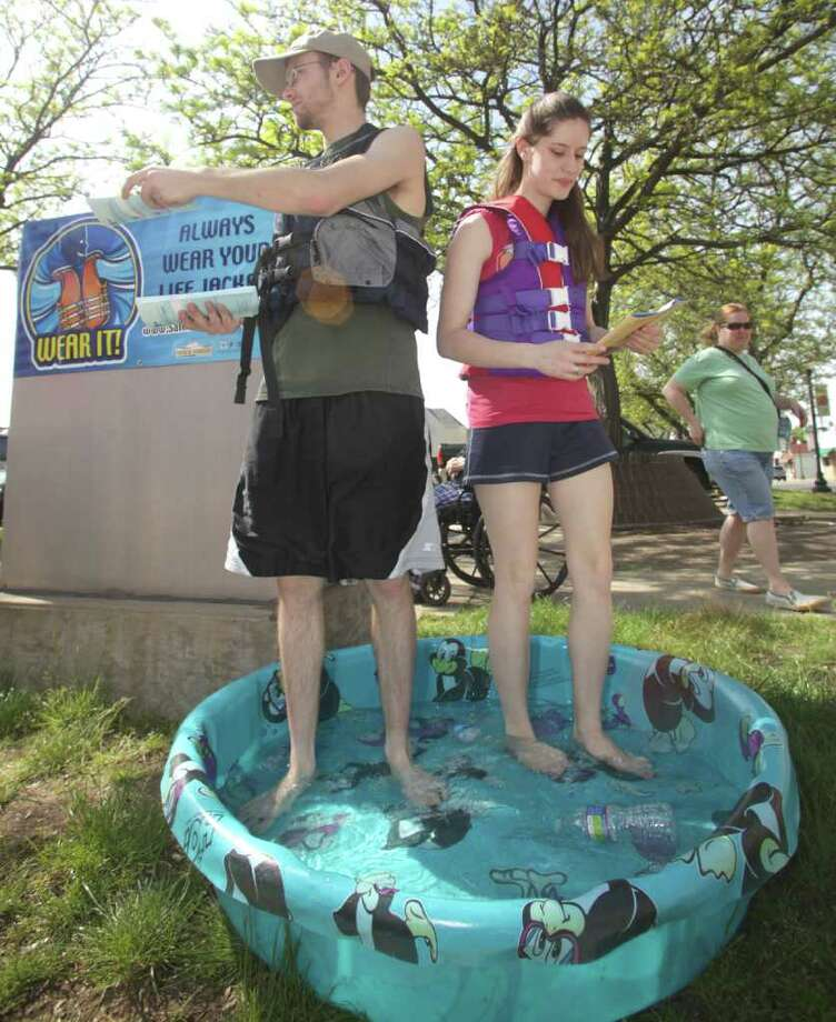 In this Saturday, May 21, 2011 photo, Bruce Crawford and Grace Nash pass out water safety brochures at the International Cuisine Festival in Painesville, Ohio. A judge sentenced the pair to stand in a tiny swimming pool while wearing life jackets and handing out the brochures in lieu of jail time, after searchers spent hours looking for them last month after they were spotted on the Grand River and they lied to an official about being in the water. (AP Photo/The News-Herald, Michael Allen Blair) Photo: Michael Allen Blair