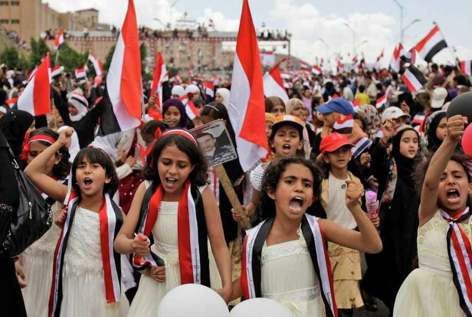 Yemeni girls chant slogans along with anti-government protestors during a ceremony to commemorate the anniversary of Yemen's reunification, in Sanaa, Yemen, Sunday, May 22, 2011. A deal for Yemeni leader Ali Abdullah Saleh to step down after 32 years in power was thrown into doubt Sunday after the ruling regime brought hundreds of loyalists into the streets to protest the pact and said he would not sign unless a public ceremony were held that included opposition leaders. A Saudi diplomat says armed loyalists of embattled Yemeni President Ali Abdullah Saleh have encircled a diplomatic mission in Sanaa, where the American, British, Saudi and European ambassadors were trapped inside. (AP Photo/Hani Mohammed) Photo: Hani Mohammed / AP