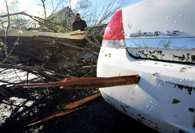 A piece of wood is lodged in the bumper of a car after at least one tornado struck parts of north Minneapolis, causing extensive property damage, killing at least one person and injuring at least 18 others, Sunday, May 22, 2011. (AP Photo/Craig Lassig) Photo: Craig Lassig