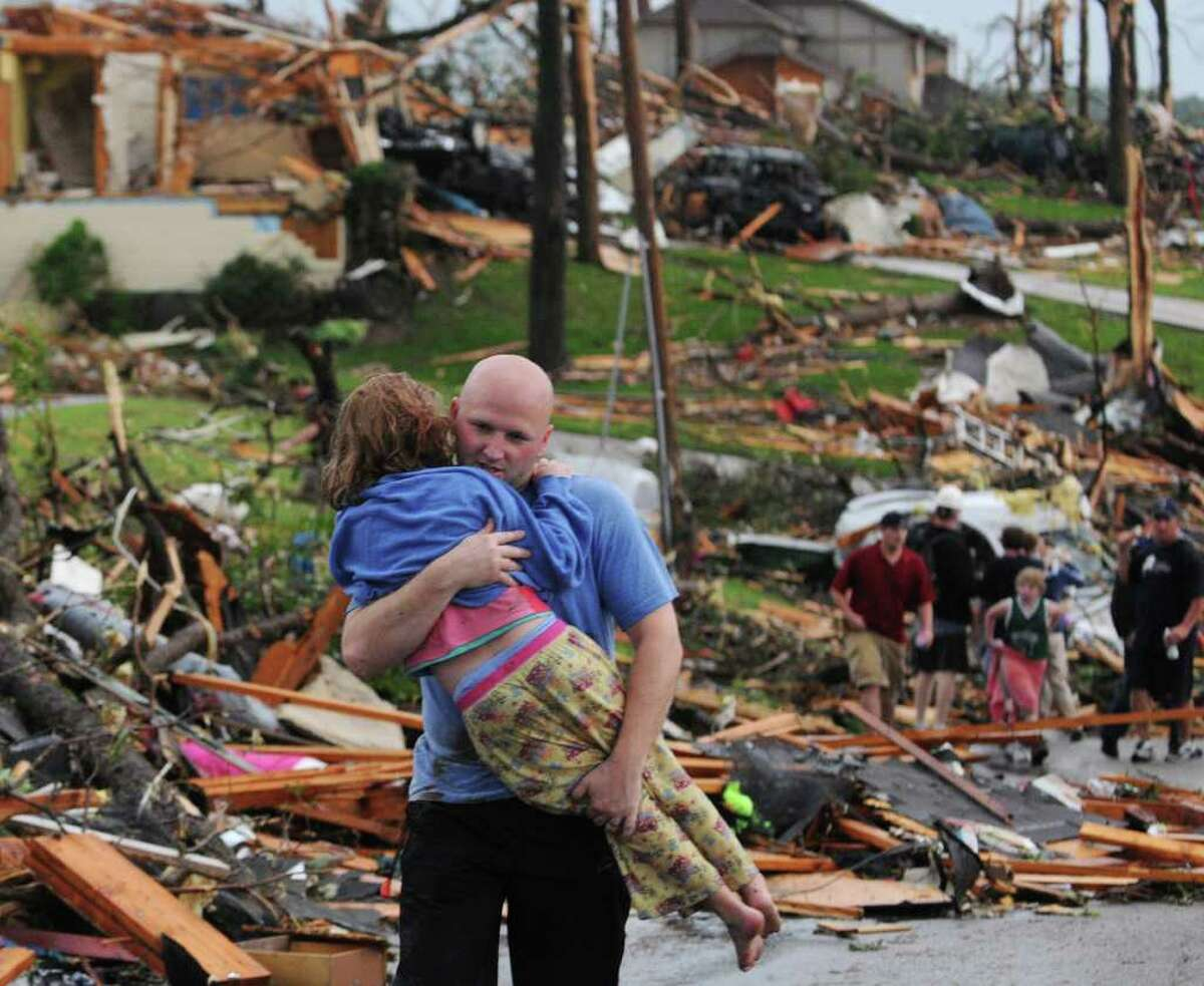 A man carries a young girl who was rescued after being trapped with her mother in their home after a tornado hit Joplin, Mo. on Sunday evening,. The tornado tore a path a mile wide and four miles long destroying homes and businesses.