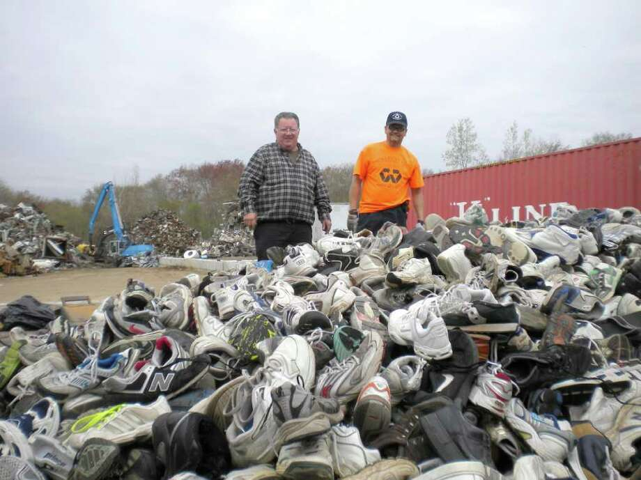 Sneakers collected during the Greenwich Recycling Advisory Board's annual used sneaker drive are dumped at Willimantic Waste, the central collection point in the state. At left, Ronnie Pucci of Greenwich Recycling looks over the haul — more than a ton and a half of sneakers — with Williwaste foreman Jose Cruz. Photo: Contributed Photo / Greenwich Citizen