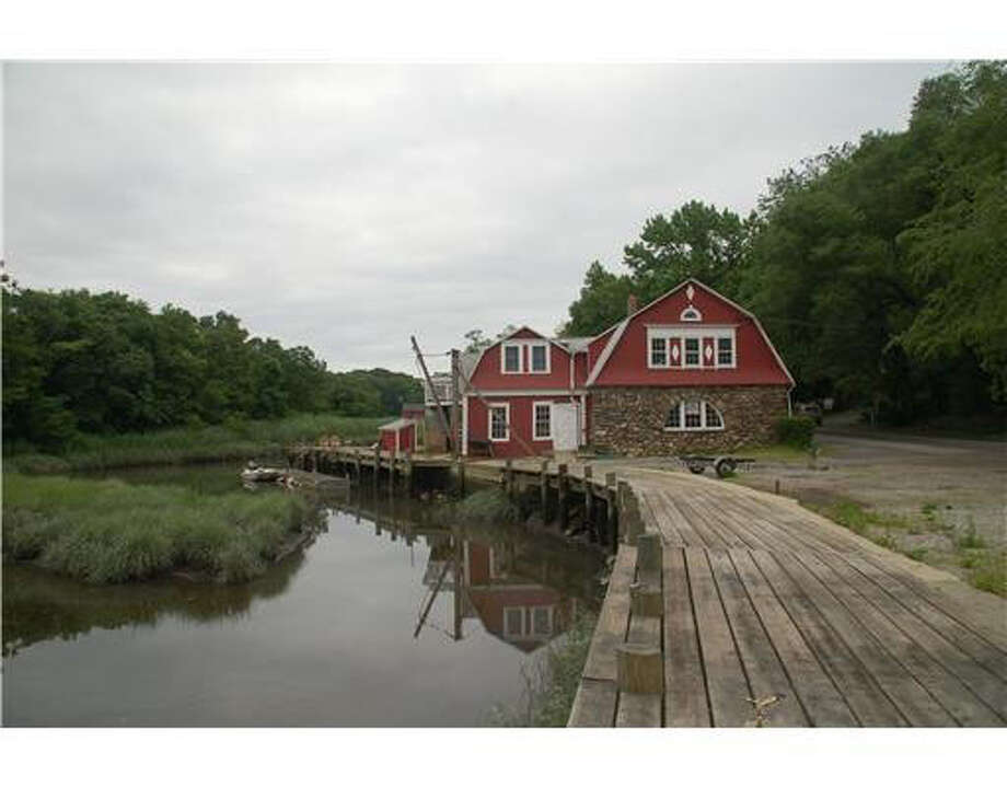 The historic red building on .32 acres on a tidal inlet off Riverside Avenue has had many lives – as a sawmill, blacksmith shop, steam laundry, boat building shop and boat repair and marine supply store, with an apartment above. Fully rented, the building still has living quarters on the second level and an exercise studio and office space on the first floor. Photo: Contributed Photo / Stamford Advocate Contributed