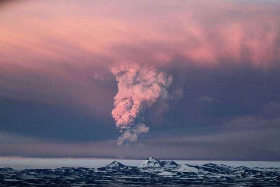 In this photo taken on Saturday, May 21, 2011,  smoke plumes from the Grimsvotn volcano, which lies under the Vatnajokull glacier, about 120 miles, (200 kilometers) east of the capital, Rejkjavik, which began erupting Saturday for the first time since 2004.  Iceland closed its main international airport and canceled domestic flights Sunday as a powerful volcanic eruption sent a plume of ash, smoke and steam 12 miles (20 kilometers) into the air. (AP Photo/Jon Gustafsson) ICELAND OUT Photo: Jon Gustafsson, AP  / AP2011
