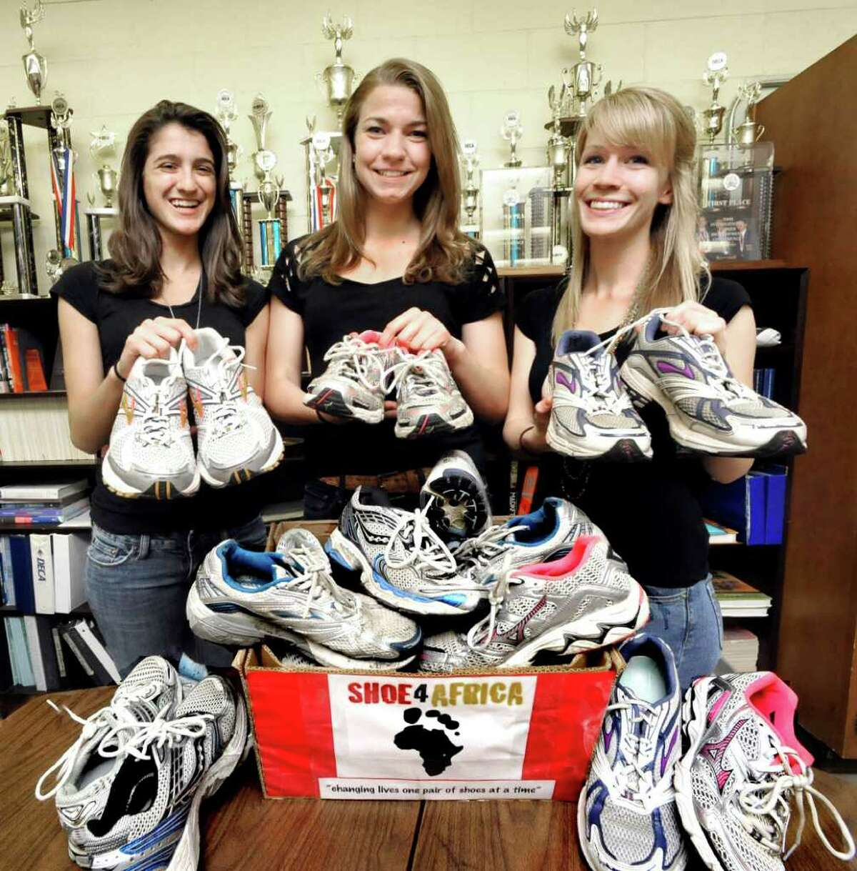 """From left, Brianna Maffucci, Allie Bukowski, and Sarah Eyman, all 18, display some of the shoes they have collected to benefit """"Shoe4Africa,"""" a program that collects running shoes and ships them to the poor in Africa. Photographed at Danbury High School on Monday, May 23, 2011."""