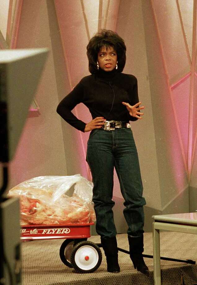 Nov. 16, 1988:  Oprah Winfrey stands in her old size 10 jeans and shows off her new figure as she stands in front of 68 pounds of fat inside a toy wagon, representing the weight she lost in four months on a liquid diet.  (AP Photo/Charles Bennet, file) Photo: Charles Bennet, STR
