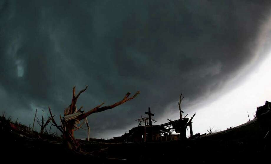 A cross stands atop a church that was severely damaged by a tornado in Joplin, Mo., as a severe storm passes overhead Monday, May 23, 2011. A large tornado moved through much of the city Sunday, damaging a hospital, hundreds of homes and businesses and killing at least 89 people. (AP Photo/Charlie Riedel) Photo: Charlie Riedel, STF / AP