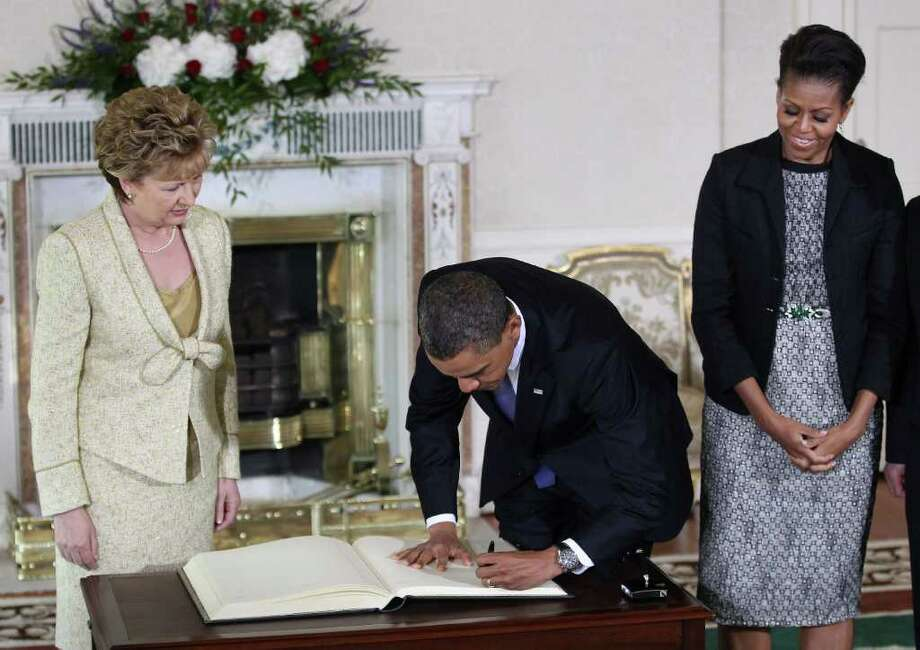 DUBLIN, IRELAND - MAY 23:  US President Barack Obama signs a visitors book as First Lady Michelle Obama (R) and President of Ireland Mary McAleese (L) look on at Áras an Uachtaráin on May 23, 2011 in Dublin, Ireland. U.S. President Obama is visiting Ireland for one day. He will meet with distant relatives in Moneygall and speak at a rally in central Dublin after a concert.  (Photo by Peter Macdiarmid/Getty Images) Photo: Peter Macdiarmid, Getty Images / 2011 Getty Images