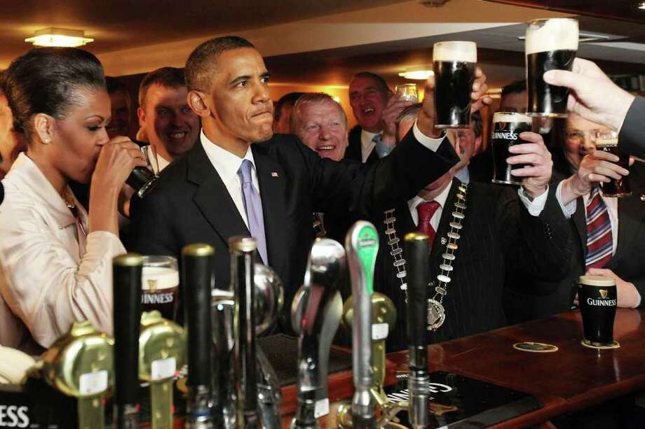 MONEYGALL, IRELAND - MAY 23: US President Barack Obama and First Lady Michelle Obama enjoy a glass of Guinness in his ancestral home of Moneygall, on May 23, 2001 in Moneygall, Ireland. U.S. President Obama is visiting Ireland for one day. He will meet with distant relatives in Moneygall and speak at a rally in central Dublin after a concert.   (Photo by Irish Government - Pool /Getty Images) Photo: Pool, Getty Images / 2011 Getty Images