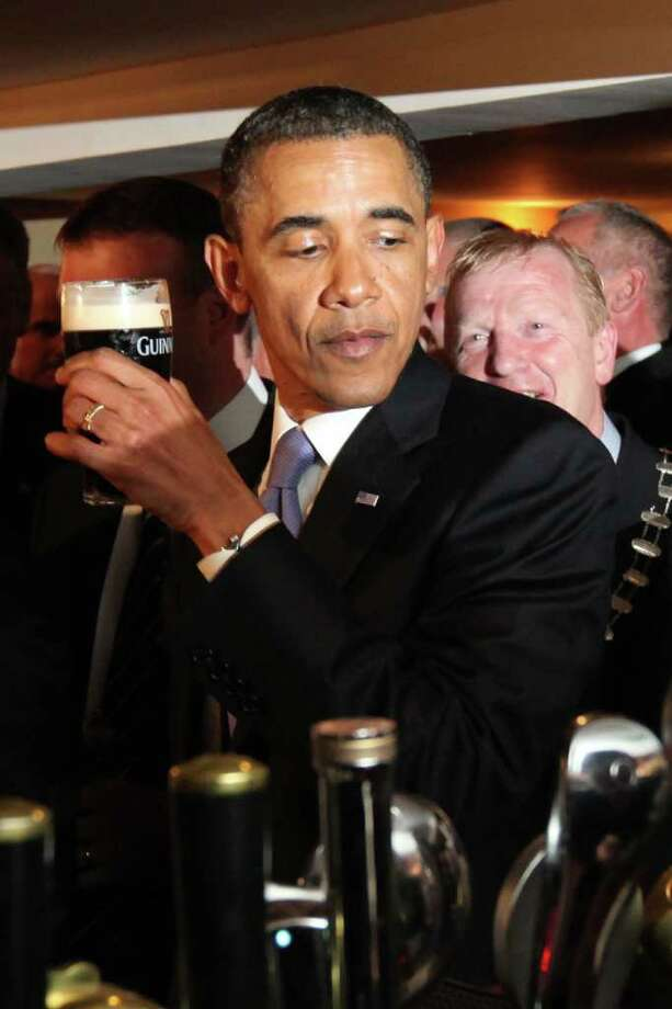 MONEYGALL, IRELAND - MAY 23:  US President Barack Obama enjoys a glass of Guinness in his ancestral home of Moneygall, on May 23, 2001 in Moneygall, Ireland. U.S. President Obama is visiting Ireland for one day at the start of a week long tour of Europe. He will meet with distant relatives in Moneygall and speak at a rally in central Dublin after a concert.   (Photo by Irish Government - Pool/Getty Images) Photo: Pool, Getty Images / 2011 Getty Images