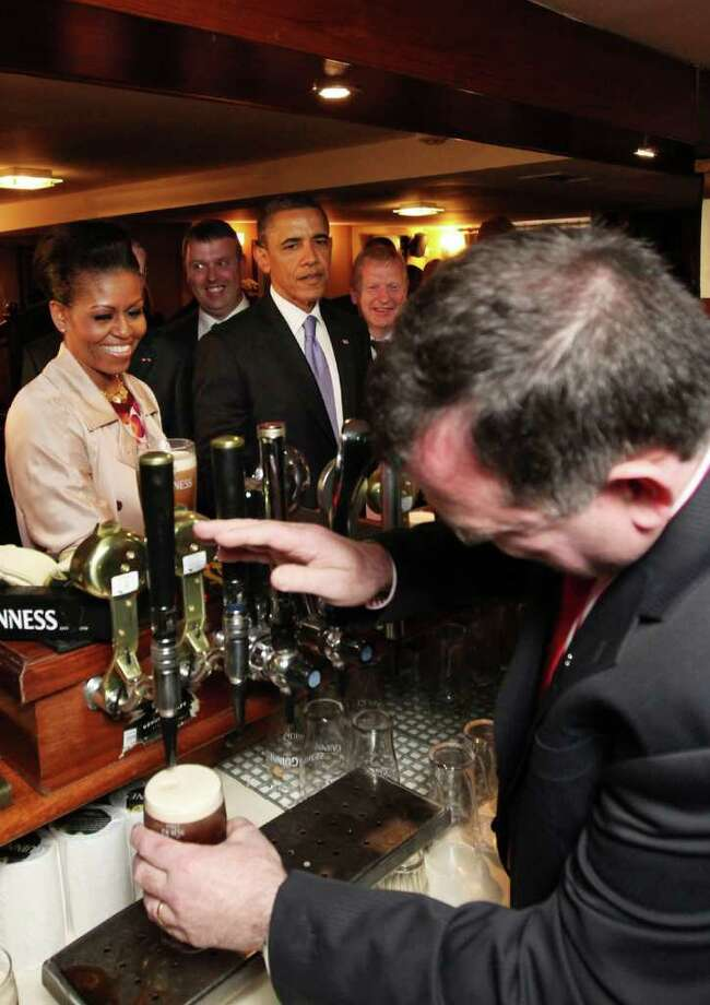 MONEYGALL, IRELAND - MAY 23:  U.S. President Barack Obama enjoys a glass of Guinness in his ancestral home of Moneygall alongside First Lady Michelle Obama (L)  on May 23, 2011 in Moneygall, Ireland. U.S. President Obama is visiting Ireland for one day at the start of a week long tour of Europe. He will meet with distant relatives in Moneygall and speak at a rally in central Dublin after a concert.   (Photo by Irish Government - Pool/Getty Images) Photo: Pool, Getty Images / 2011 Getty Images