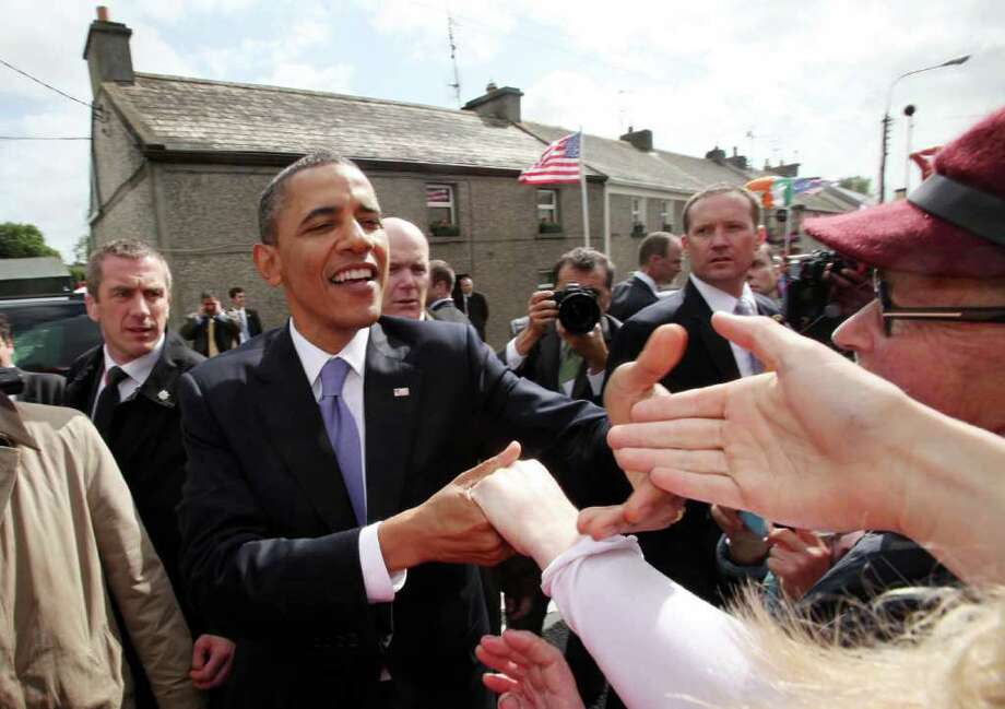 MONEYGALL, IRELAND - MAY 23:  U.S. President Barack Obama greets the locals in his ancestral home of Moneygall alongside First Lady Michelle Obama (L)  on May 23, 2011 in Moneygall, Ireland. U.S. President Obama is visiting Ireland for one day at the start of a week long tour of Europe. He will meet with distant relatives in Moneygall and speak at a rally in central Dublin after a concert.   (Photo by Irish Government - Pool/Getty Images) Photo: Getty Images