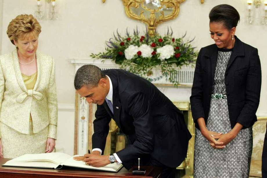 DUBLIN, IRELAND - MAY 23: (L - R) Irish President Mary McAleese and first lady Michelle Obama watch as U.S. President Barack Obama signs the vistor's book at Aras an Uachtarain, the official residence of the President of Ireland, May 23, 2011 in Dublin, Ireland.  Obama is visiting Ireland for one day. He will meet with distant relatives in Moneygall and speak at a rally in central Dublin after a concert.  (Photo by Irish Government - Pool /Getty Images) Photo: Pool, Getty Images / 2011 Getty Images