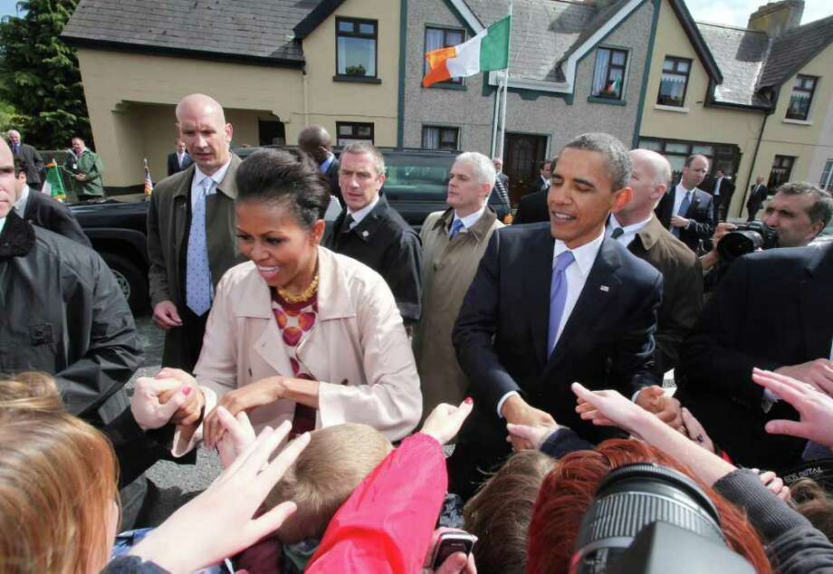 MONEYGALL, IRELAND - MAY 23:  U.S. President Barack Obama and First Lady Michelle Obama greet the locals in his ancestral home of Moneygall alongside First Lady Michelle Obama (L)  on May 23, 2011 in Moneygall, Ireland. U.S. President Obama is visiting Ireland for one day at the start of a week long tour of Europe. He will meet with distant relatives in Moneygall and speak at a rally in central Dublin after a concert.   (Photo by Irish Government - Pool/Getty Images) Photo: Getty Images