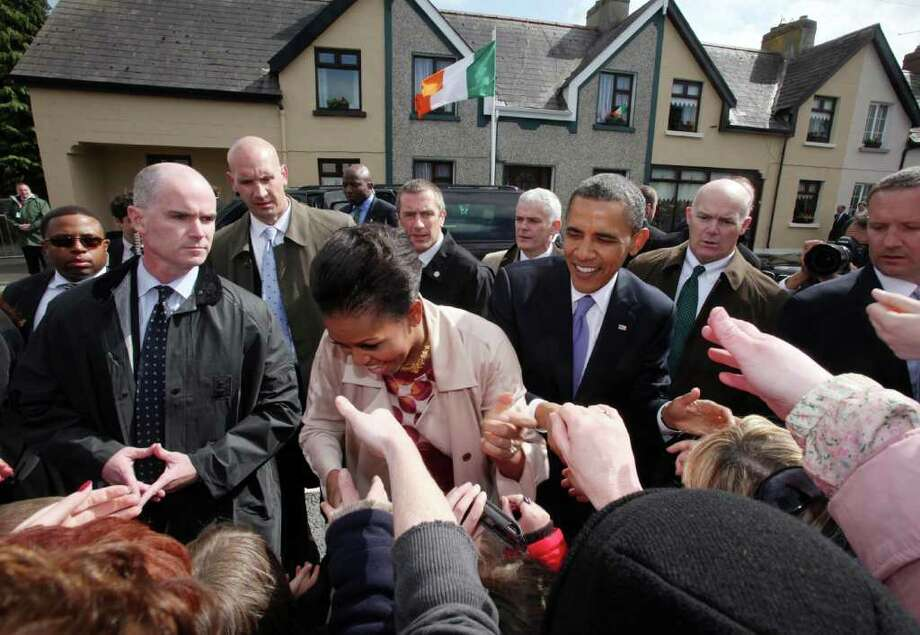 MONEYGALL, IRELAND - MAY 23:  U.S. President Barack Obama and First Lady Michelle Obama greet the locals in his ancestral home of Moneygall alongside First Lady Michelle Obama (L)  on May 23, 2011 in Moneygall, Ireland. U.S. President Obama is visiting Ireland for one day at the start of a week long tour of Europe. He will meet with distant relatives in Moneygall and speak at a rally in central Dublin after a concert.   (Photo by Irish Government - Pool/Getty Images)