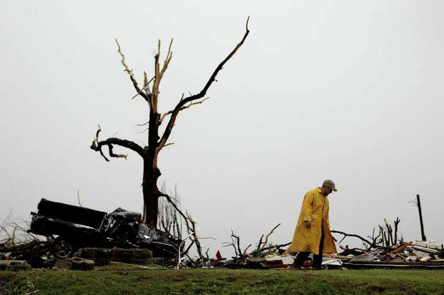 A firefighter searches a home Monday, May 23, 2011, that was destroyed by a tornado in Joplin, Mo. A large tornado moved through much of the city Sunday, damaging a hospital and hundreds of homes and businesses and killing at least 89 people. (AP Photo/Charlie Riedel) Photo: Charlie Riedel, AP / AP2011