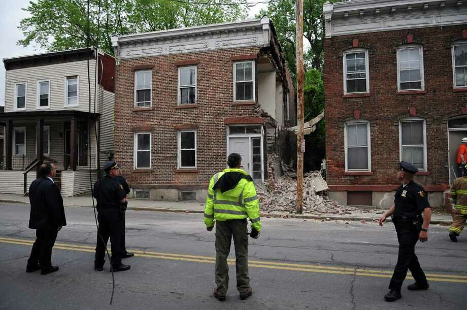 Officials assess the damage of a partially collapsed building on 15th Street near the RPI campus on Monday  May 23, 2011 in Troy, NY. The building  was unoccupied at the time, as was the building at left. The building at right was occupied. ( Philip Kamrass / Times Union) Photo: Philip Kamrass