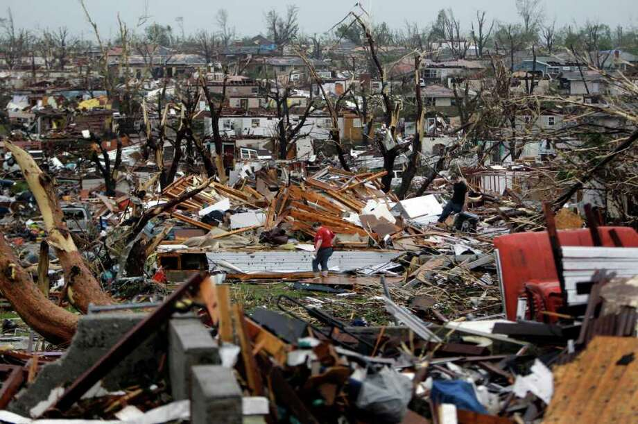 Meghan Miller stands in the middle of a destroyed neighborhood as she checks on her sister-in-law's home Monday, May 23, 2011, in Joplin , Mo. A large tornado moved through much of the city Sunday, damaging a hospital and hundreds of homes and businesses. (AP Photo/Jeff Roberson) Photo: Jeff Roberson