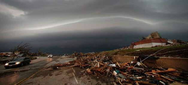 A shelf cloud containing a thunderstorm approaches a tornado-ravaged neighborhood in Joplin, Mo., Monday, May 23, 2011. A large tornado moved through much of the city Sunday, damaging a hospital, hundreds of homes and businesses and killing at least 89 people. (AP Photo/Charlie Riedel) Photo: Charlie Riedel