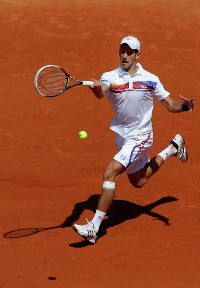 Novak Djokovic of Serbia returns the ball to Thiemo de Bakker of The Netherlands during the first round match of the French Open tennis tournament at Roland Garros stadium in Paris, Monday May 23, 2011. (AP Photo/Christophe Ena) Photo: Christophe Ena