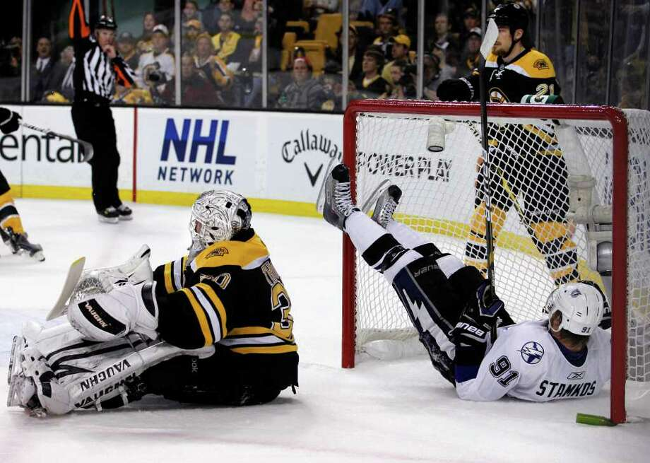 Tampa Bay Lightning center Steven Stamkos (91) lands in the net after his scoring bid was denied by Boston Bruins defenseman Andrew Ference, behind, and goalie Tim Thomas (30) in the first period of Game 5 of the NHL hockey Stanley Cup playoffs Eastern Conference finals, in Boston on Monday, May 23, 2011. (AP Photo/Elise Amendola) Photo: Elise Amendola