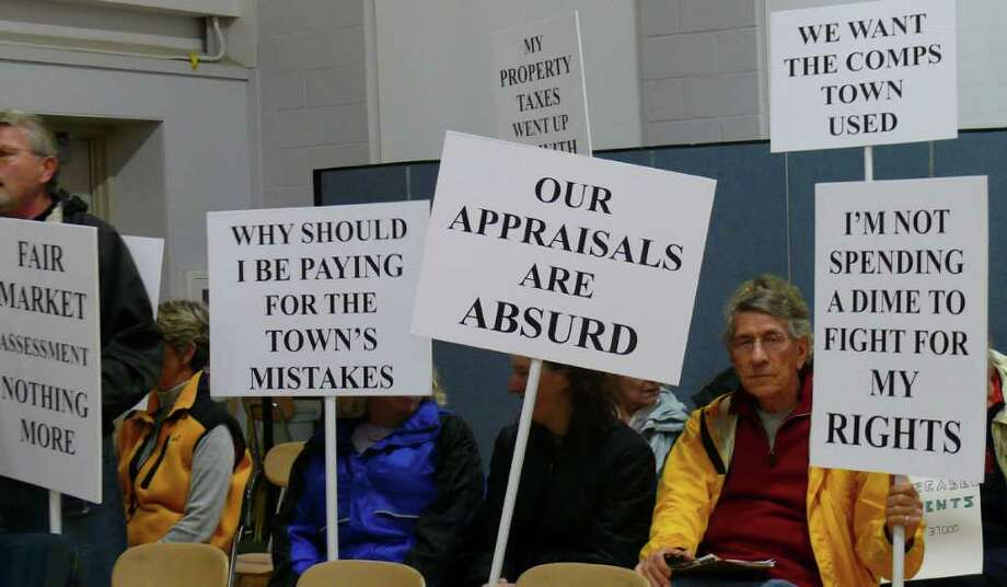 Property owners in the Pine Creek neighborhood hold signs at the Representative Town Meeting denouncing the new assessments set for their homes during the recent townwide revaluation. Photo: Genevieve Reilly / Fairfield Citizen