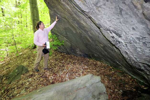 "Jeff Cordulack, communications for Audubon Greenwich, explores the rock overhang at Audubon Greenwich where the person known as ""The Leatherman,"" a wandering hobo dressed in a leather outfit, was reported to have stayed when walking through Greenwich during the early 1860s through the late 1880s, Tuesday afternoon, May 10, 2011. Photo: Bob Luckey / Greenwich Time"