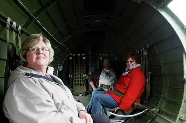 "Carol Thomson left, the volunteer coordinator for the Museum of Flight gets ready for take of aboard the WWII era B-17 named the ""Aluminum Overcast.""  On May 23, 2011 the Experimental Aircraft Association offered scenic flights to local journalists from the Museum of Flight at the Seattle Municipal Airport. Photo: Joe Dyer / SEATTLEPI.COM"