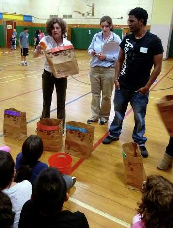 Sacred Heart University Assistant Clinical Professor of Exercise Science Wendy Bjerke, left, goes through food group containers that were part of a relay race run at Fit Kids Field Day at Fox Run Elementary School in Norwalk. Photo: Contributed Photo;/ Mike Lauterborn, Contributed Photo / Norwalk Citizen