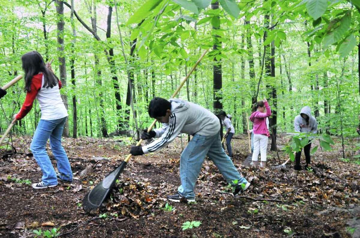 Juan Estanislado, 13, joins a group of students from Scofield Magnet Middle School as they clear the property during the groundbreaking ceremony for the new Nature Explore Classroom at the Bartlett Arboretum & Gardens in Stamford, Conn. on Tuesday May 24, 2011.