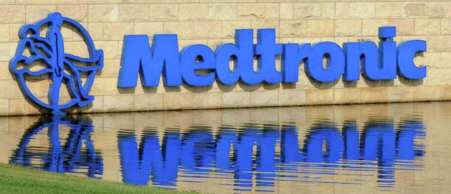 FILE - In this file photo taken Aug. 24, 2010, medical device maker Medtronic's logo reflects in the pond in front of the corporate headquarters, in Fridley, Minn. Medtronic, the world's largest medical device maker, said Tuesday, May 24, 2011, its fourth-quarter net income dropped 19 percent on expenses related to its recent layoffs.(AP Photo/Jim Mone, file) Photo: Jim Mone
