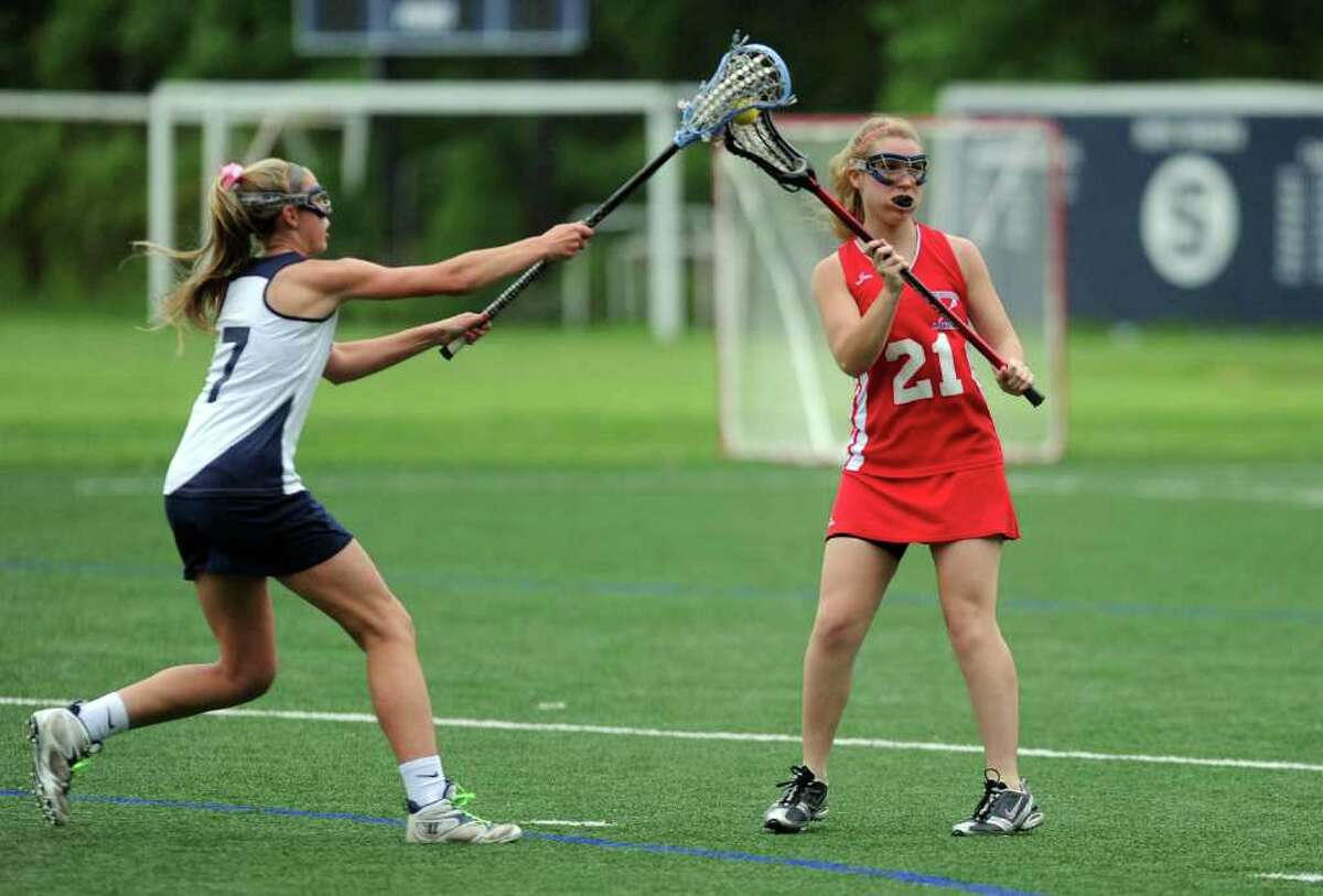 Staples High School lacrosse player Maeve Flaherty, left, reaches to block a shot last week. Flaherty was one of nine lacrosse players from six different schools whose eligibility was reinstated by the Connecticut Interscholastic Athletic Conference Tuesday morning, 24 hours after they were sanctioned for violating state rules.