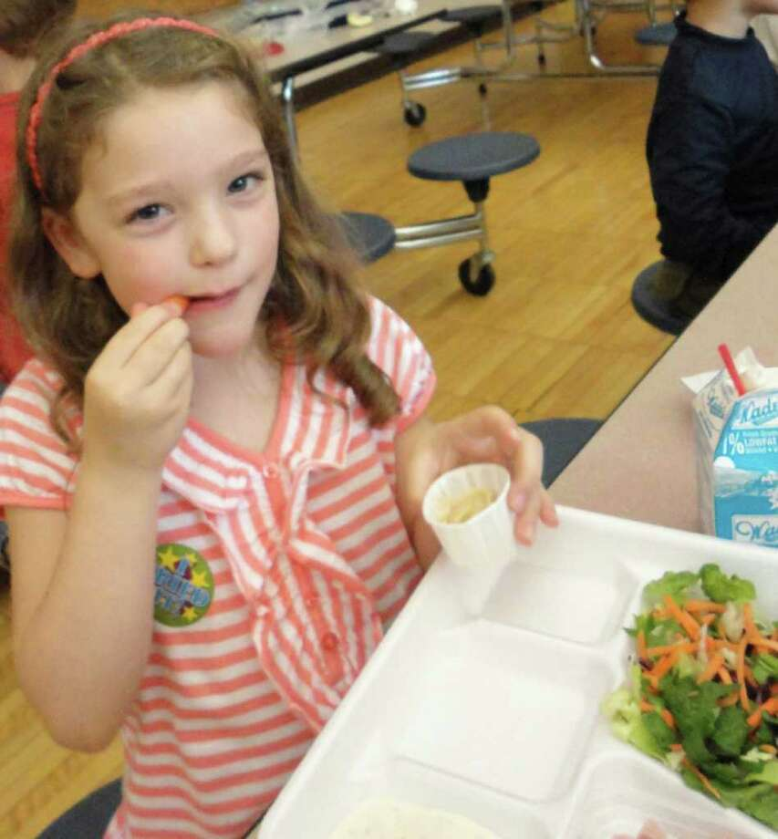 """Riley Gold, 6, enjoys hummus at North Stratfield School during a monthly """"Sample Day"""" at the cafeteria when children are encouraged to try healthy foods. Photo: Meg Barone / Fairfield Citizen freelance"""