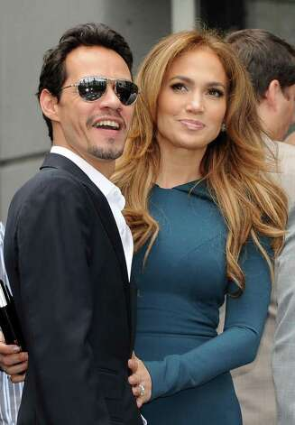 Singer Mark Anthony and his wife singer/actress Jennifer Lopez, look on as producer Simon Fuller unveils his star at the ceremony honoring him with a Hollywood Walk of Fame star, held in Hollywood, California on May 23, 2011        AFP PHOTO/Mark RALSTON Photo: MARK RALSTON, AFP/Getty Images / 2011 AFP
