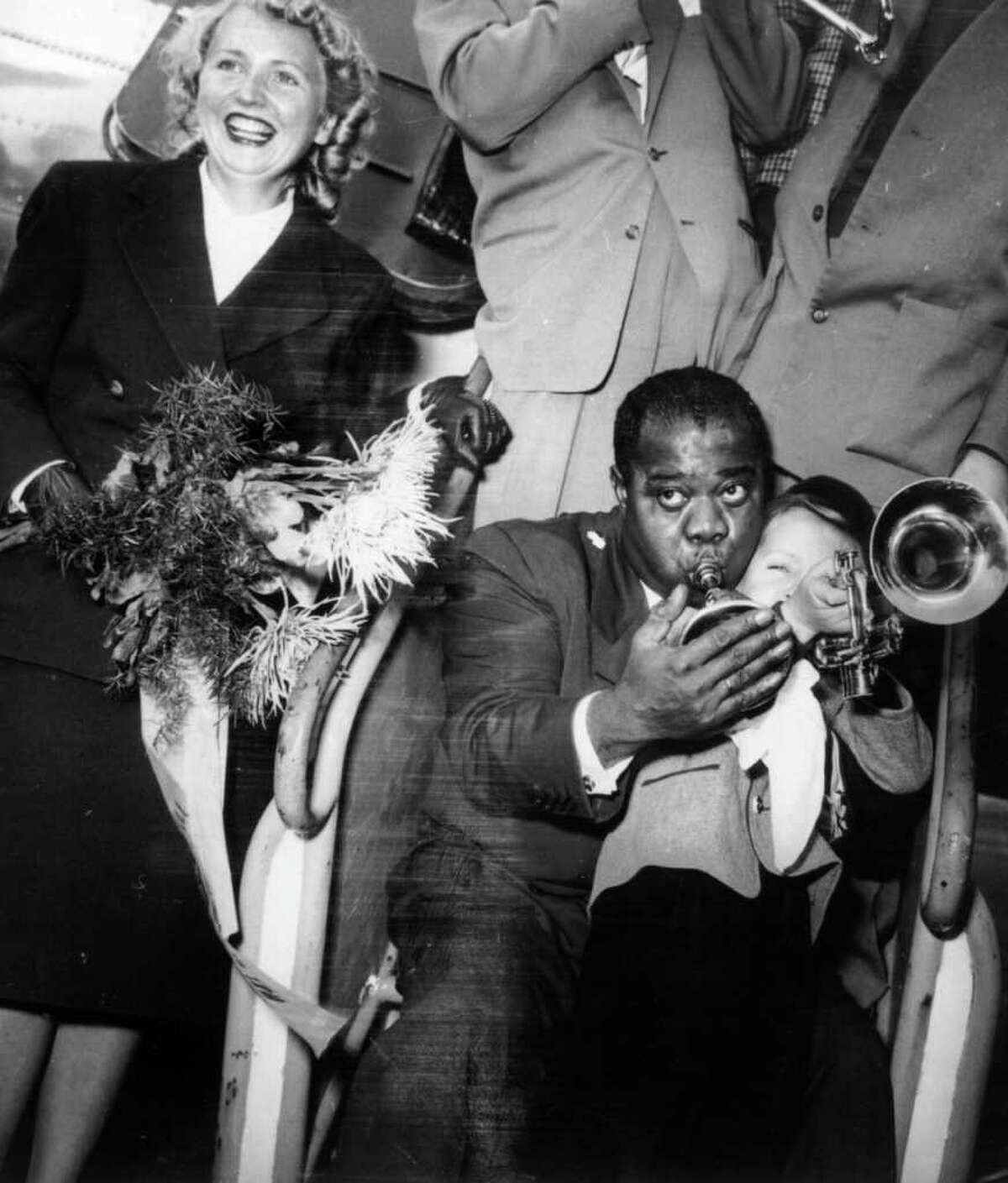 Once upon a time, music stars only added to glamor of air travel. These days, most of them seem as frazzled as the rest of us, even though they ride up front in the sardine can. Then they have to deal with the paparazzi. Let's start near the beginning, with this scene of jazz trumpeter and singer Louis Armstrong blowing horns with a young fan after arriving at Dusseldorf Airport on October 10, 1952.