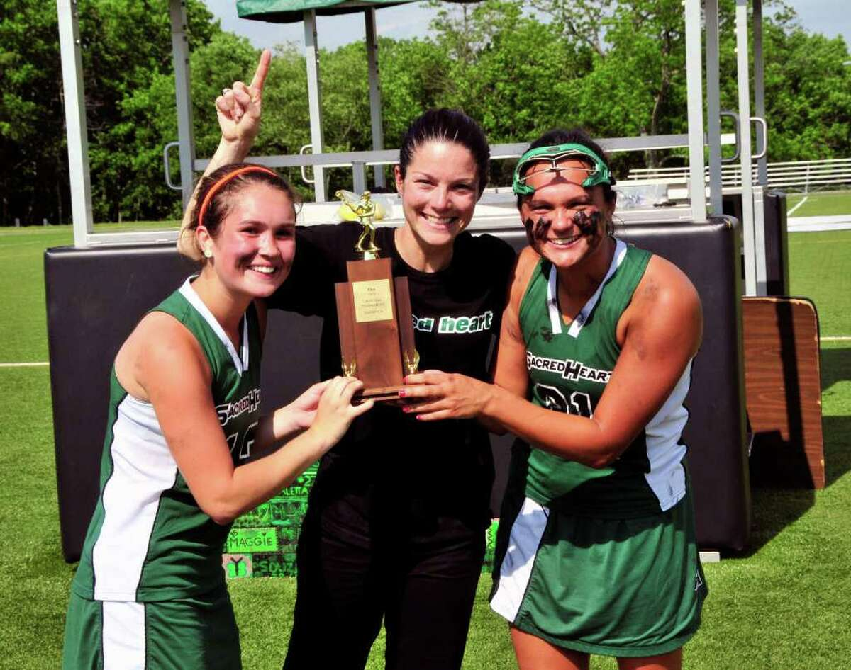 Sacred Heart co-captains Megan Cincotta, left, coach Courtney DePeter, center and Emily Hatton smile with the championship trophy after beating Greenwich Academy in the FAA lacrosse championship.