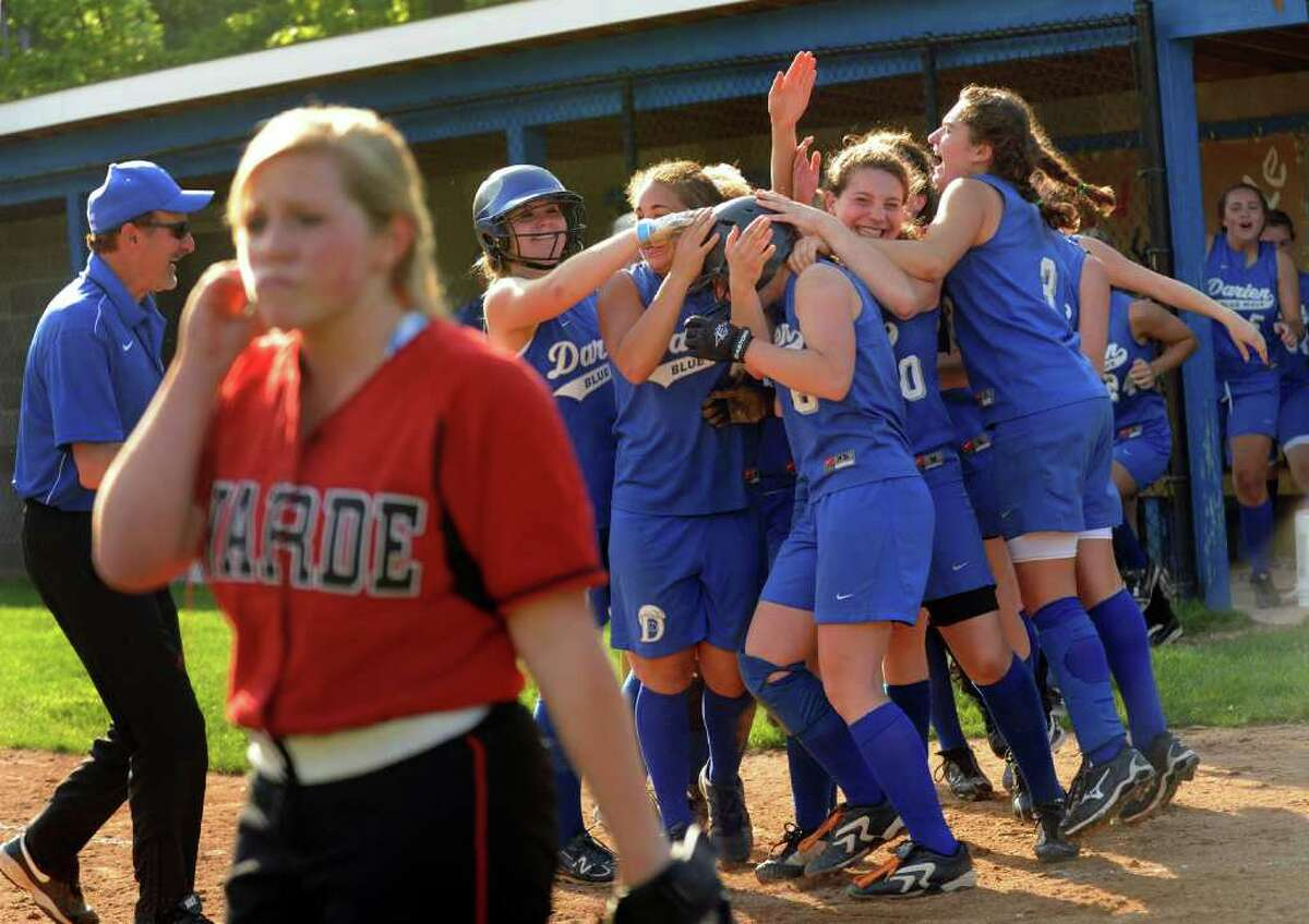 Fairfield Warde's #4 Heather VanDerheyden walks away from home plate as Darien surrounds #6 Olivia Gozdz who brought in the run to break the tie in the eighth inning to win 5-4, during girls FCIAC softball quarterfinals in Darien on Tuesday May 24, 2011.