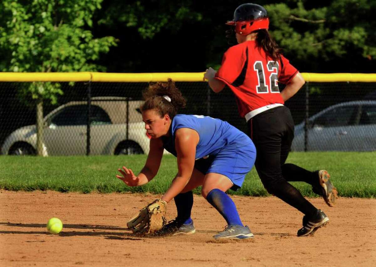Darien's #7 Nicole Buch prepares to grab a grounder as Fairfield Warde's #12 Julia Palmieri heads towards third, during girls FCIAC softball quarterfinals in Darien on Tuesday May 24, 2011.