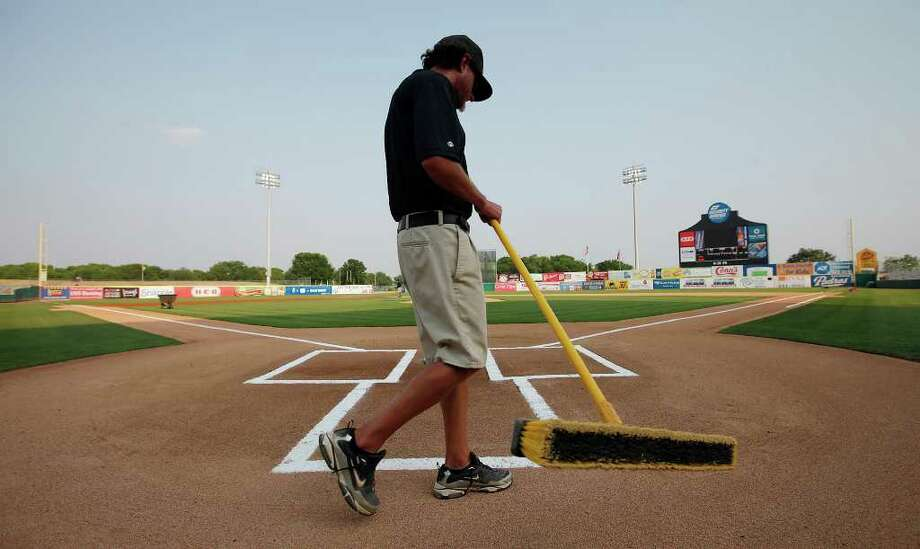 Missions' assistant groundskeeper Dan Looney sweeps around home plate at Wolff Stadium before the team's game against the Frisco Roughriders on Friday, May 20, 2011. Kin Man Hui/kmhui@express-news.net Photo: KIN MAN HUI, Kin Man Hui/Express-News / San Antonio Express-News